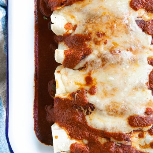 White baking dish filled with vegetarian enchiladas topped with enchilada sauce and melted cheese.