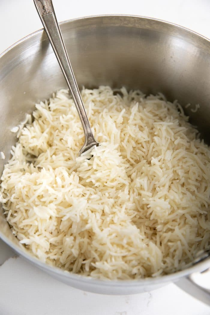 Fluffing a pot of white basmati rice.