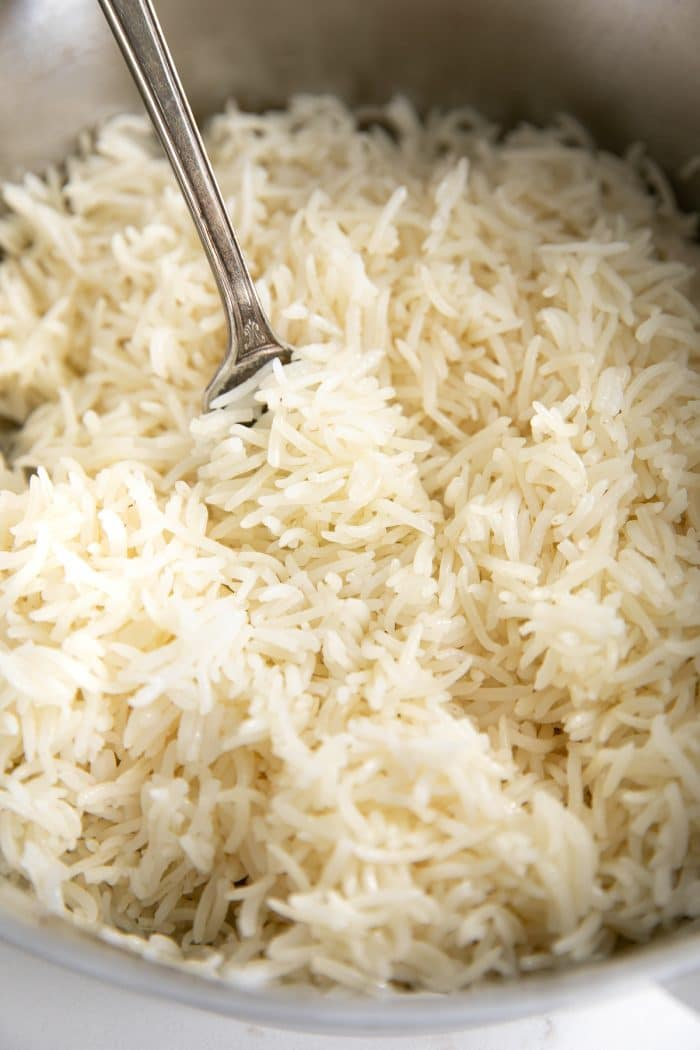 Perfectly cooked tender grains of white basmati rice in a medium pot.