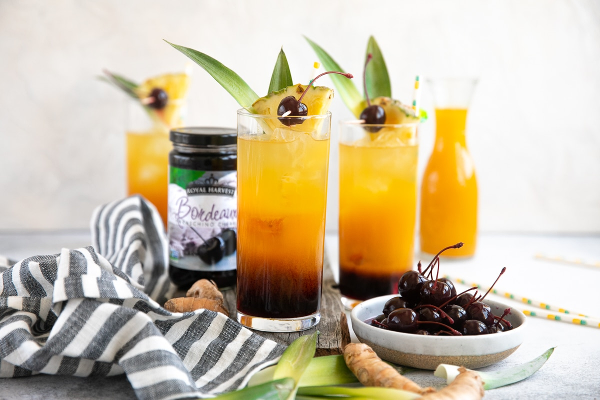 Tropical Turmeric Painkillers topped with Maraschino Cherries and pineapple leaves.
