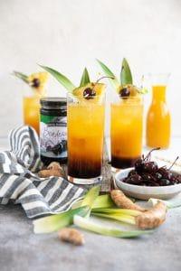 Three prepared tropical turmeric painkiller cocktails make with three layers - maraschino cherry juice, turmeric juice, and pineapple rum.