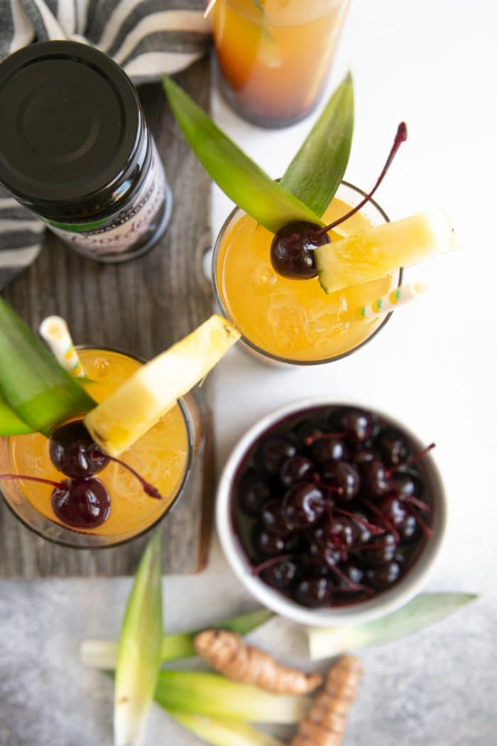 Overhead image of pineapple tropical painkillers with maraschino cherries.