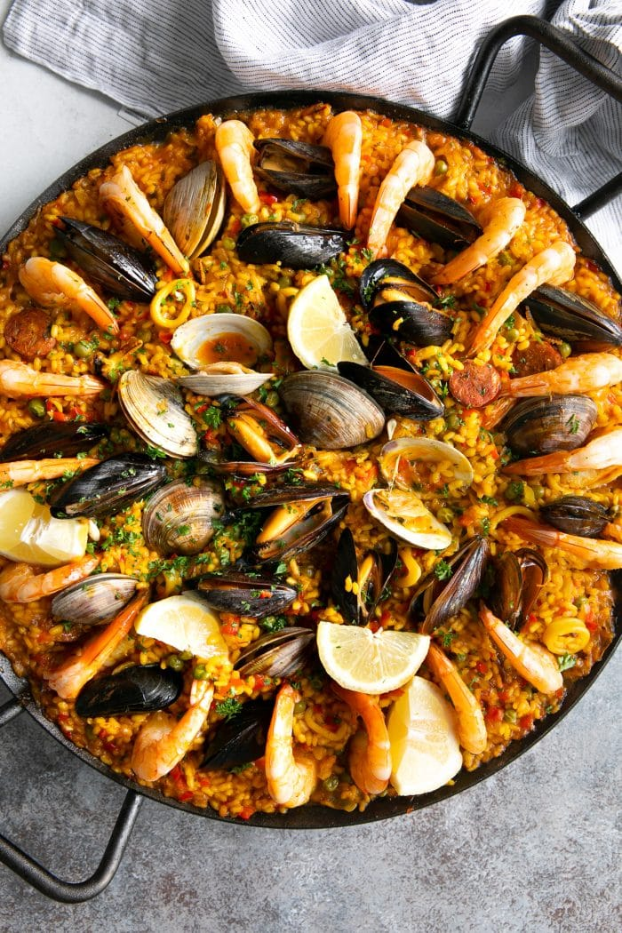 Large paella pan filled with cooked seafood and sausage paella.