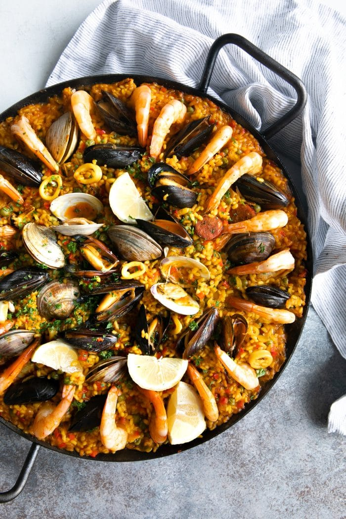 Seafood and sausage Spanish paella in a large cast iron paella pan.