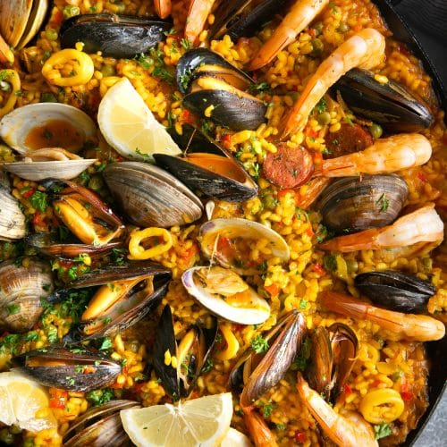 Paella filled with mussels, clams, shrimp, calamari, spanish chorizo, and saffron rice.