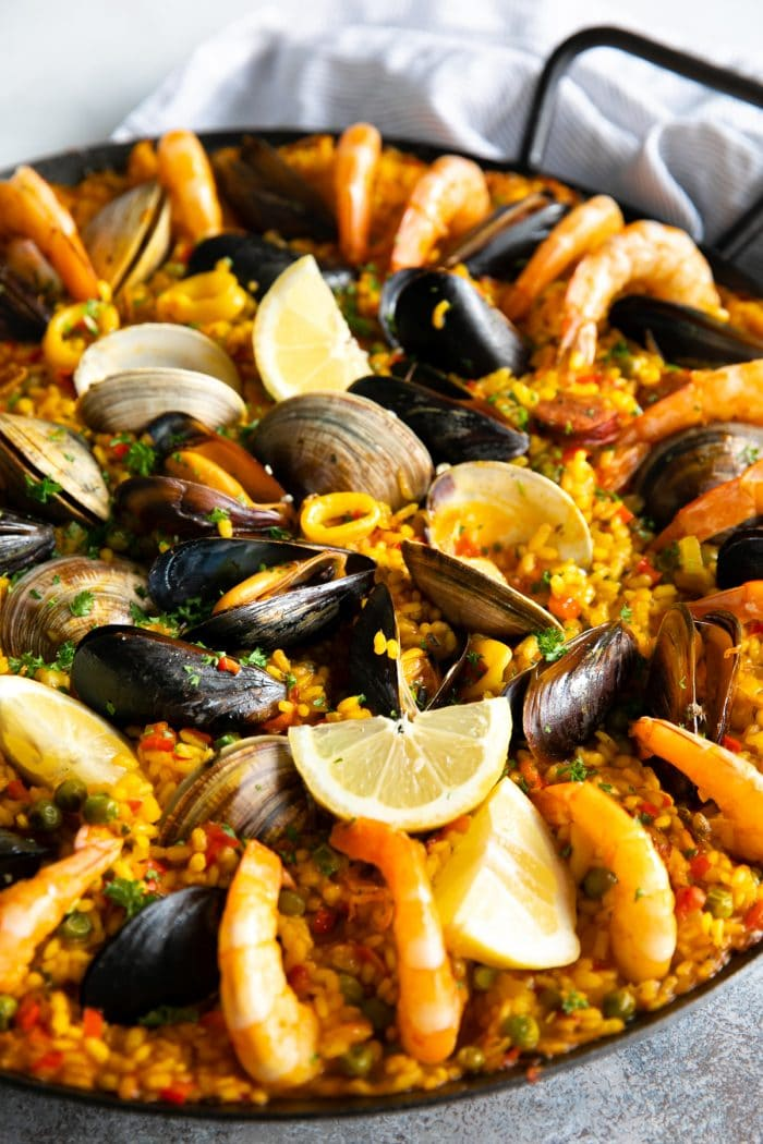 Spanish paella recipe in a large paella pan garnished with lemon wedges and chopped parsley.
