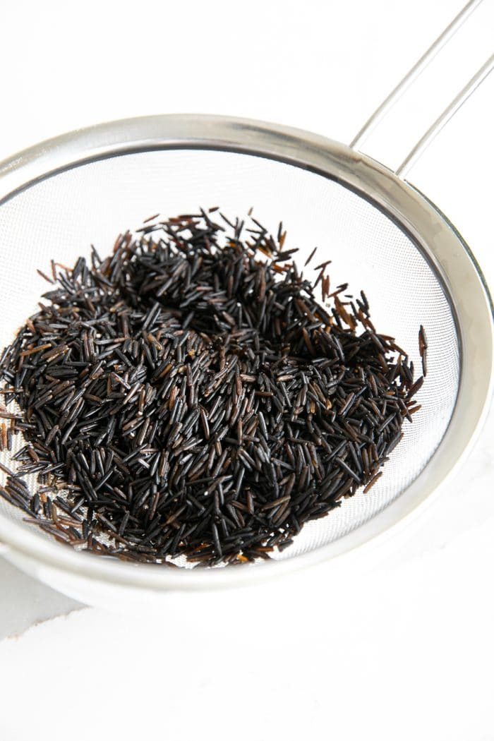 Fine-mesh strainer resting over a glass bowl and filled with wild rice.