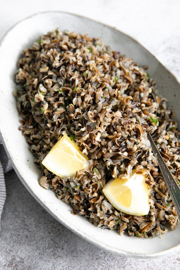 Oval-shaped serving dish filled with cooked wild rice garnished with fresh parsley and lemon wedges.