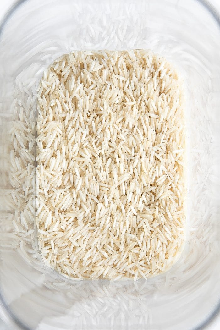 Plastic storage container filled with dry white basmati rice.