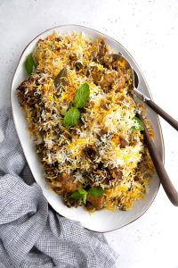 Large platter filled with cooked lamb and chicken biryani recipe.