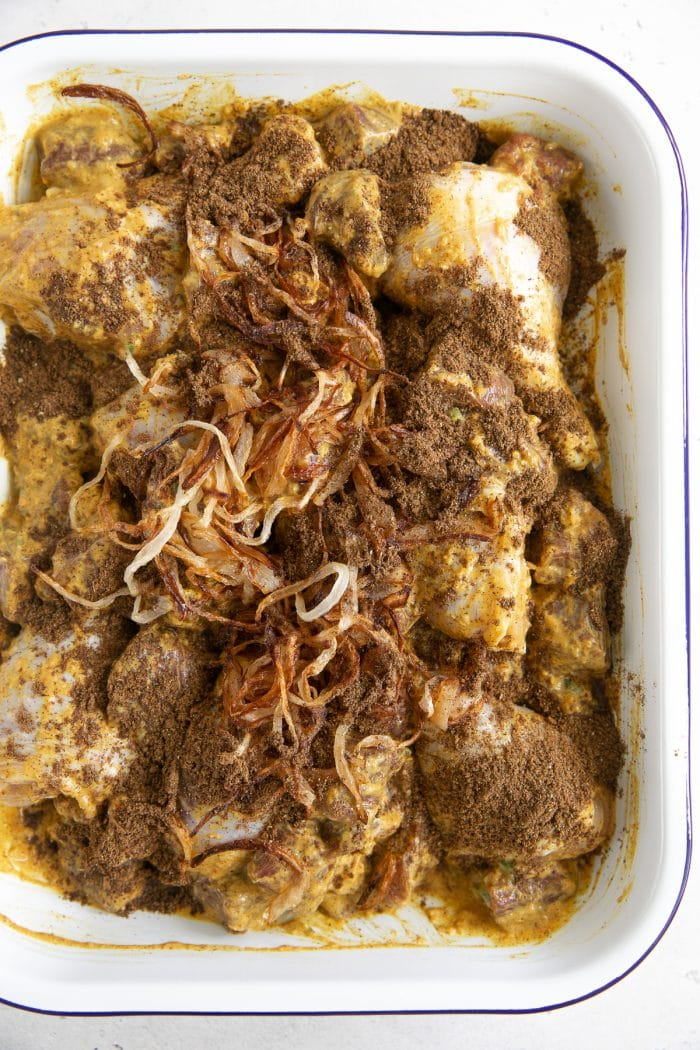 Chicken and lamb marinating in yogurt and spices in a large baking dish.