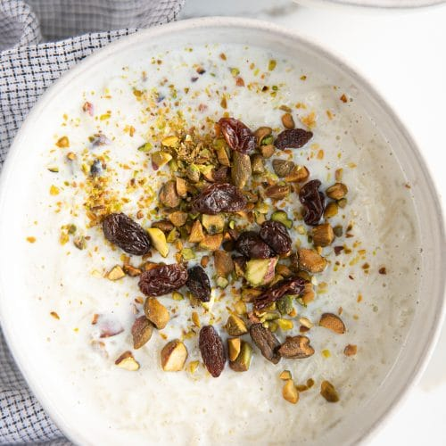 Small white dessert bowl filled with cardamom spiced Indian rice pudding and garnished with crushed pistachios and raisins.