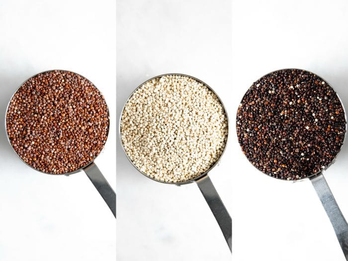 Measuring cups filled with different colored quinoa.