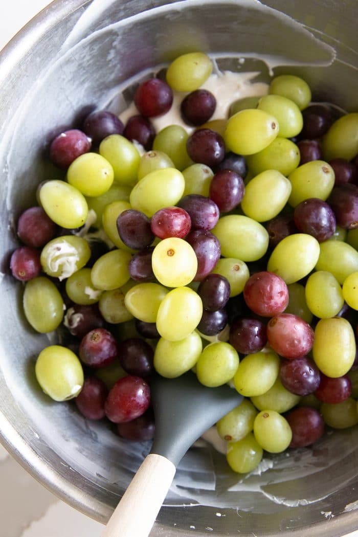 Large mixing bowl filled with washed red and green grapes.