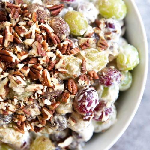 Large white serving bowl filled with red and green grapes mixed with cream cheese, sugar, sour cream, vanilla extract, and chopped pecans.