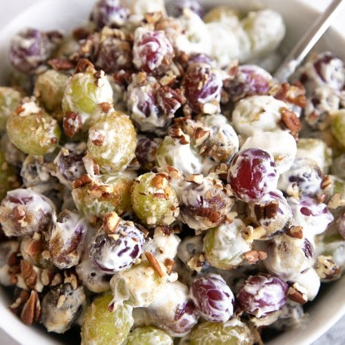 Creamy grape salad tossed with nuts and sprinkled with brown sugar.