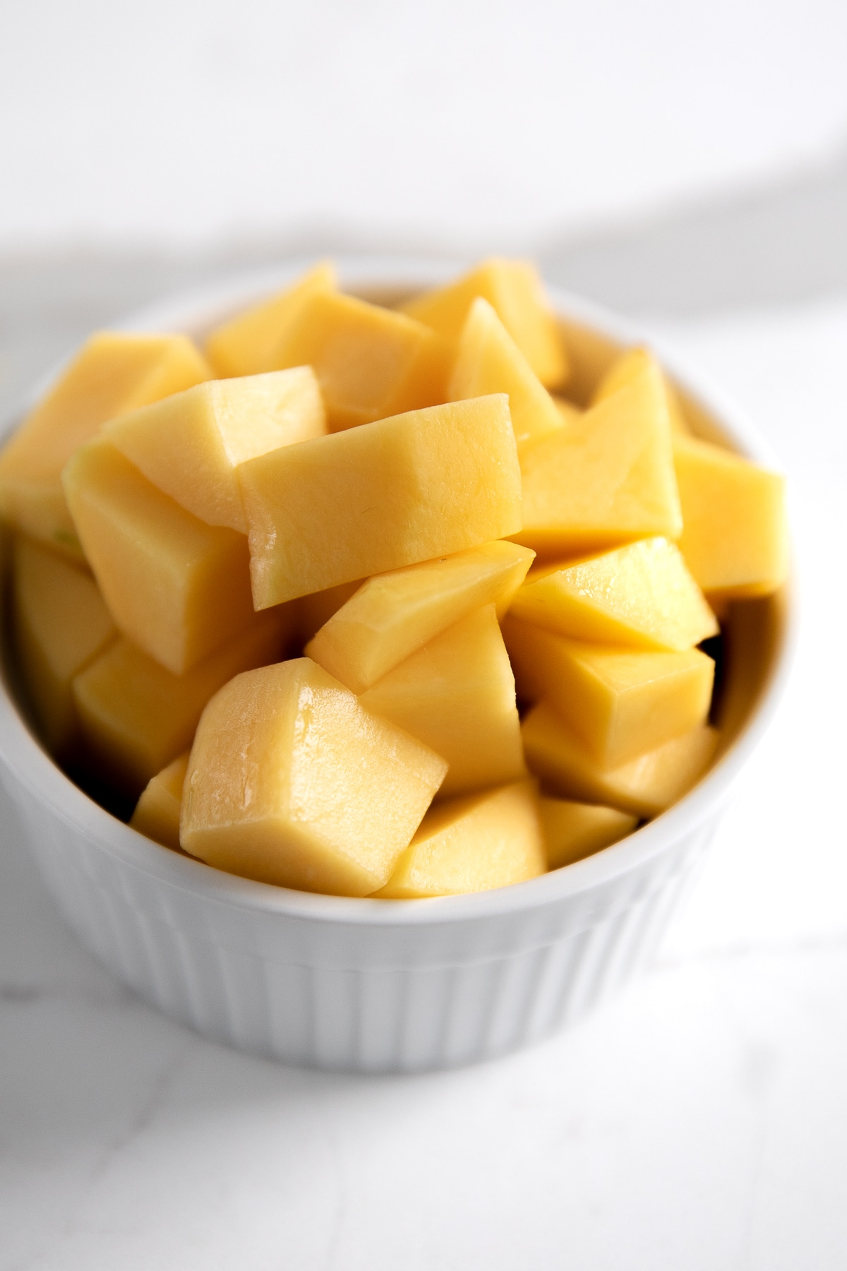 White dish filled with cubes of cut up mango.