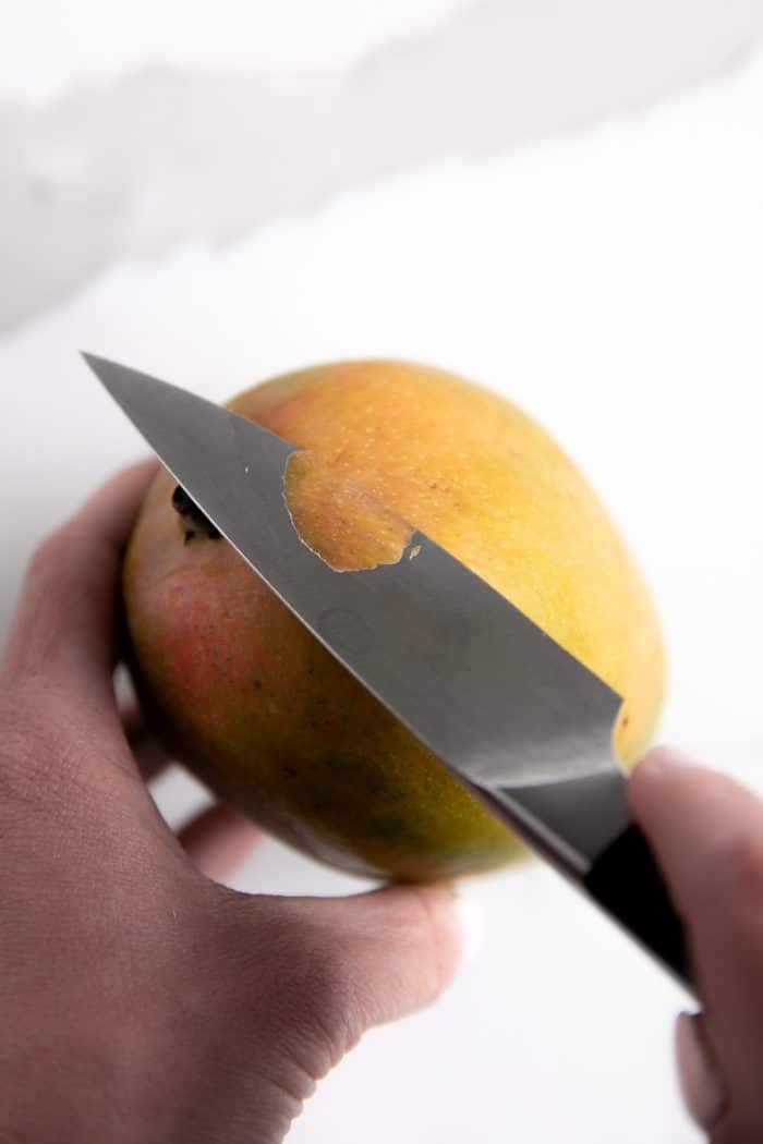 Peeling a mango before cuttinng.