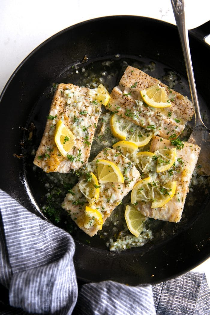 Four mahi mahi fillets in a large skillet covered with a homemade lemon butter sauce and garnished with fresh parsley.