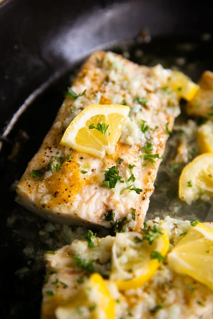 Skillet filled with fully cooked mahi mahi fillets cooked in a lemon butter sauce and garnished with fresh parsley.
