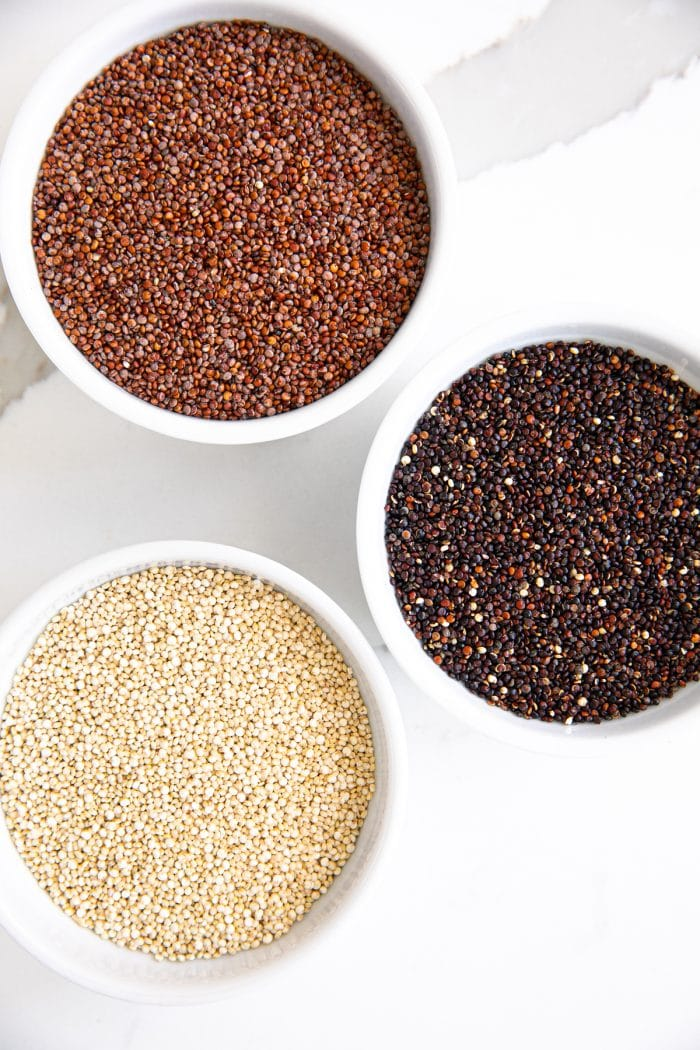 Bowls filled with red, black, and white quinoa.