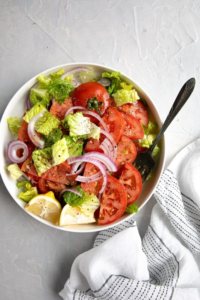 Large serving platter filled with sliced tomatoes, Romaine lettuce, sliced red onion, and homemade vinaigrette.