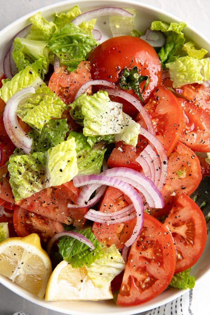 Close-up overhead image of fresh summer tomatoes sliced and served with chopped romaine lettuce and sliced red onions all drizzled with homemade vinaigrette.