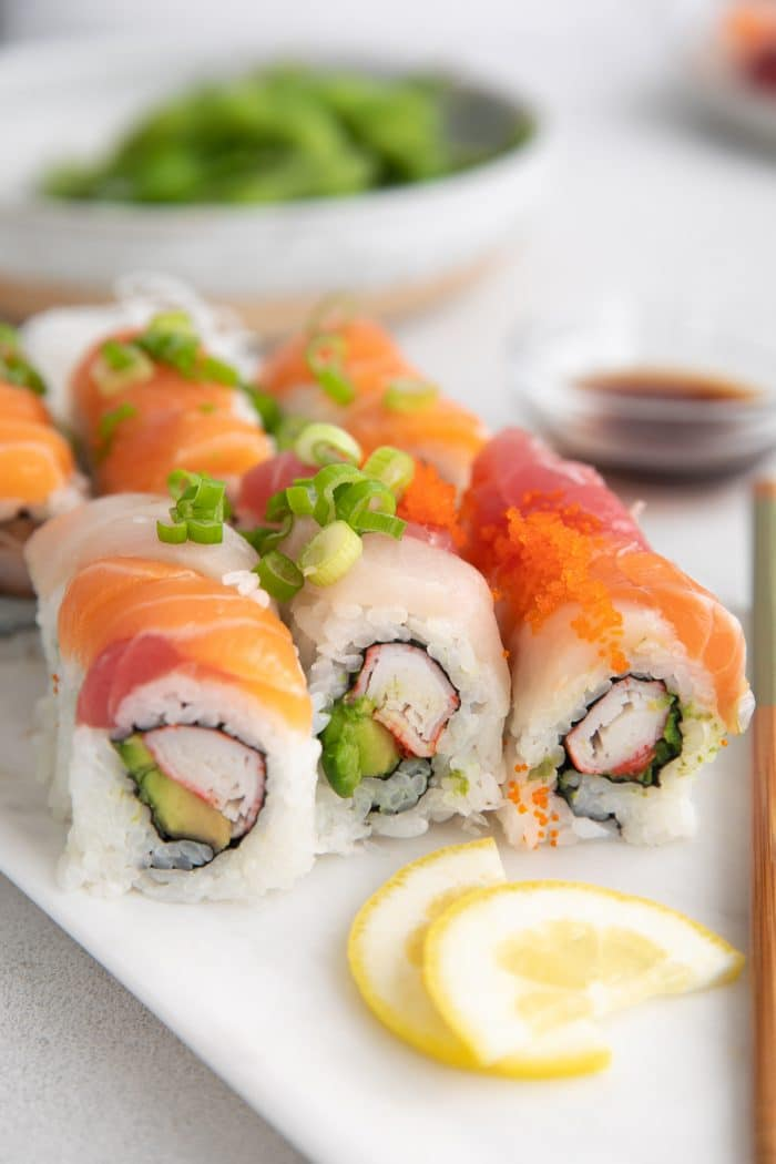 Platter filled with two popular sushi rolls with different colored fish and toppings.