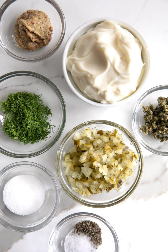 Individual ingredients for tartar sauce in their own individual glass bowls.