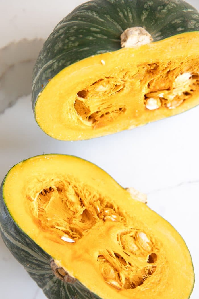 One whole kabocha squash cut in half.