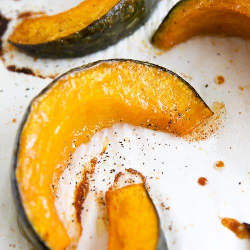 Tender roasted wedges of kabocha squash on a large baking sheet.