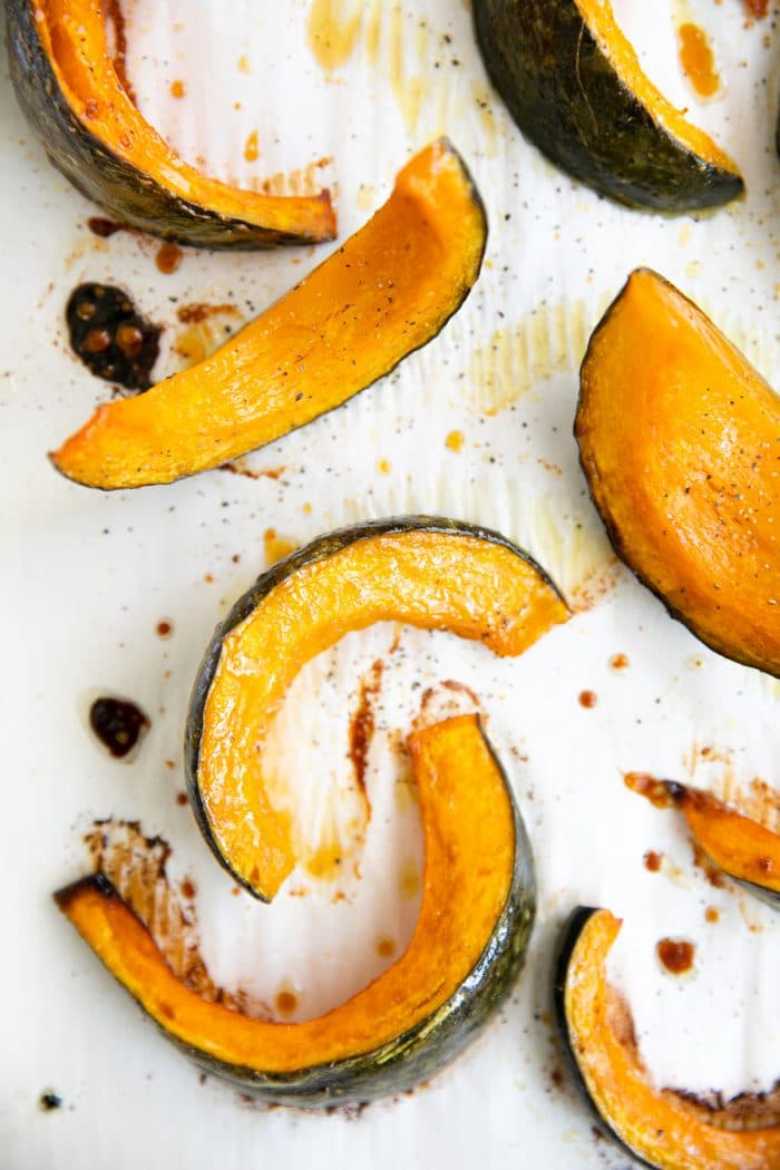 Tender roasted wedges of kabocha squash on a large baking sheet.