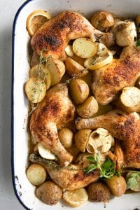 Baking pan filled with whole chicken legs, tender potatoes, sliced lemon, garlic cloves, and fresh herbs.