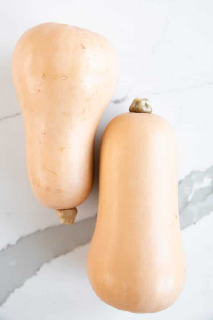 Two whole butternut squash side by side.