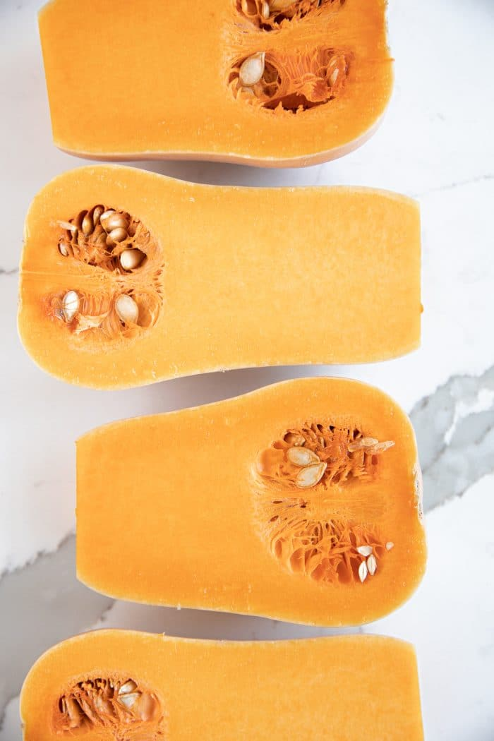 Four butternut squash halves cut-side-up in a row side by side.