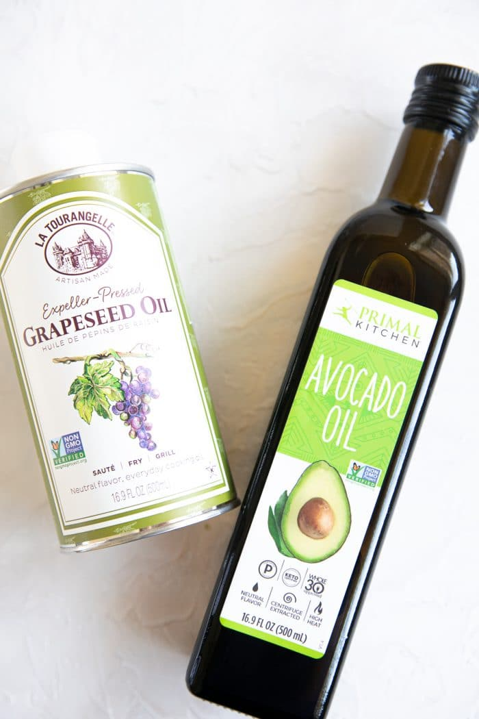 A bottle of grapeseed oil and a bottle of avocado oil