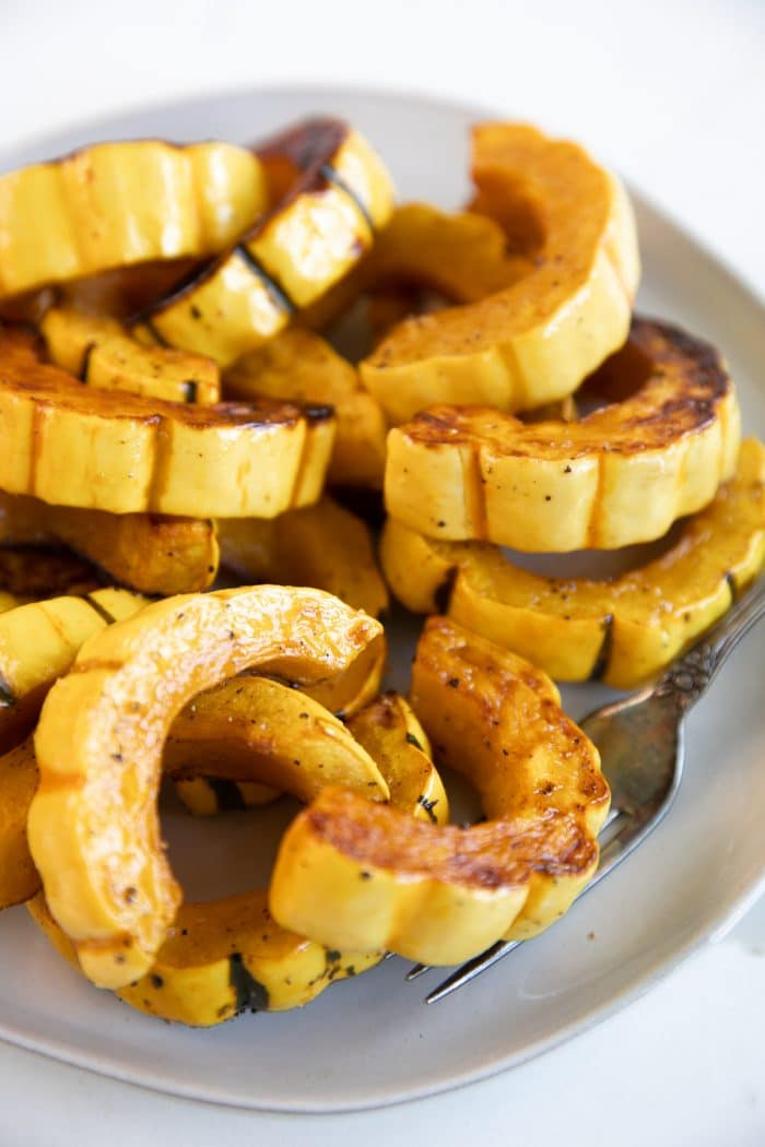 White serving plate filled with oven-roasted delicata squash.