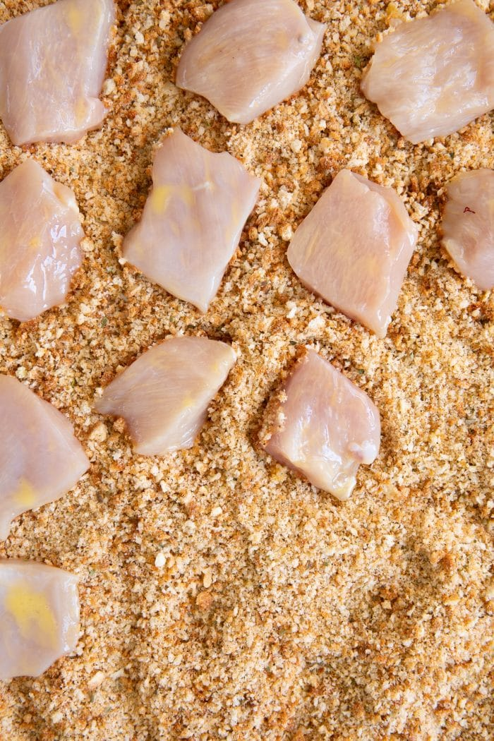 Coating raw chicken pieces in toasted panko breadcrumbs.