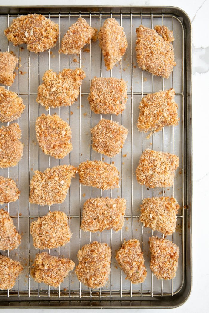 Uncooked chicken nuggets covered in spices and panko breadcrumbs on a wire rack.