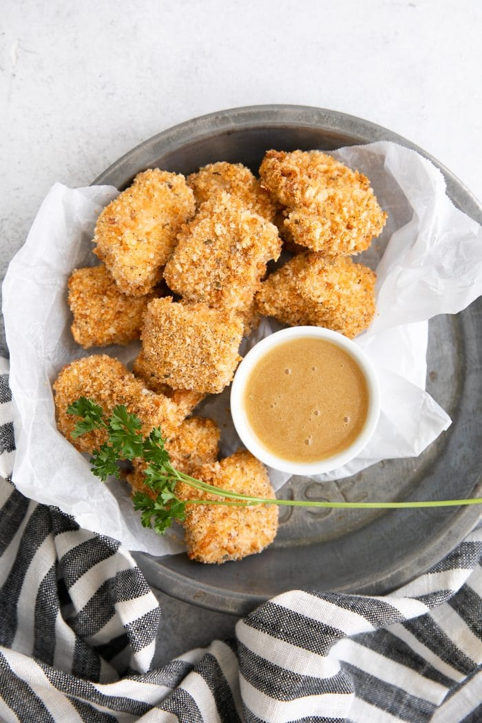 Small tray lined with parchment paper and filled with homemade baked chicken nuggets with a side of honey mustard sauce for dipping.
