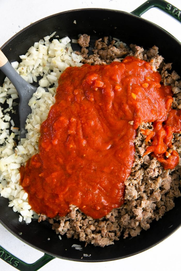 Large skillet filled with sauteed onions, browned Italian sausage, and tomato sauce.