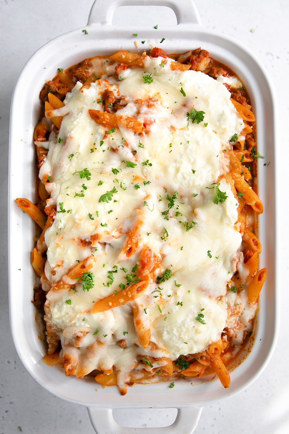 Large white baking dish filled with cheese covered and baked mostaccioli cooked in an Italian sausage and tomato pasta sauce.