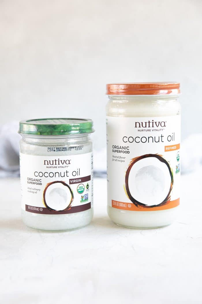 Two jars of coconut oil, one that is refined, and one that is not refined.