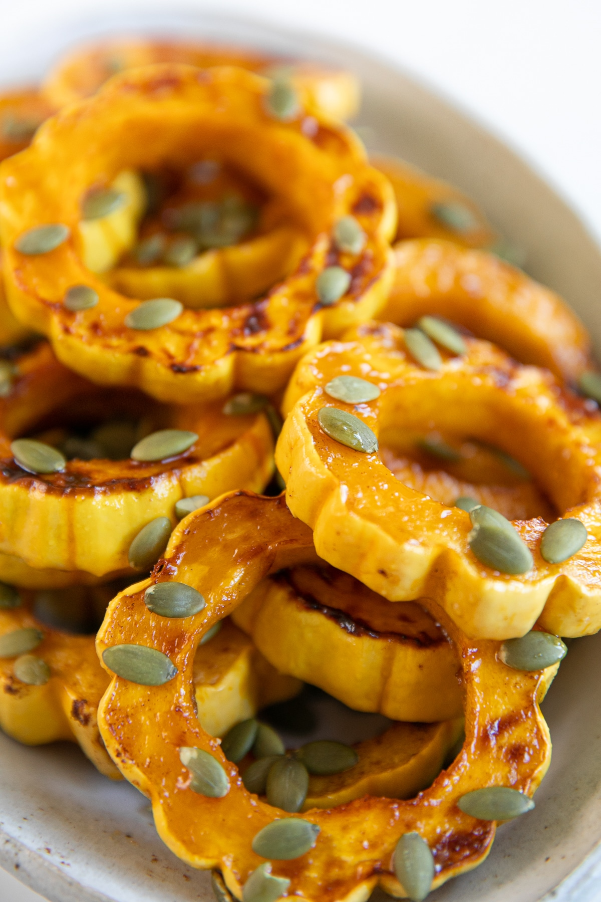 White platter filled with roasted delicata squash rings roasted in maple syrup, cinnamon, and sprinkled with pepitas.