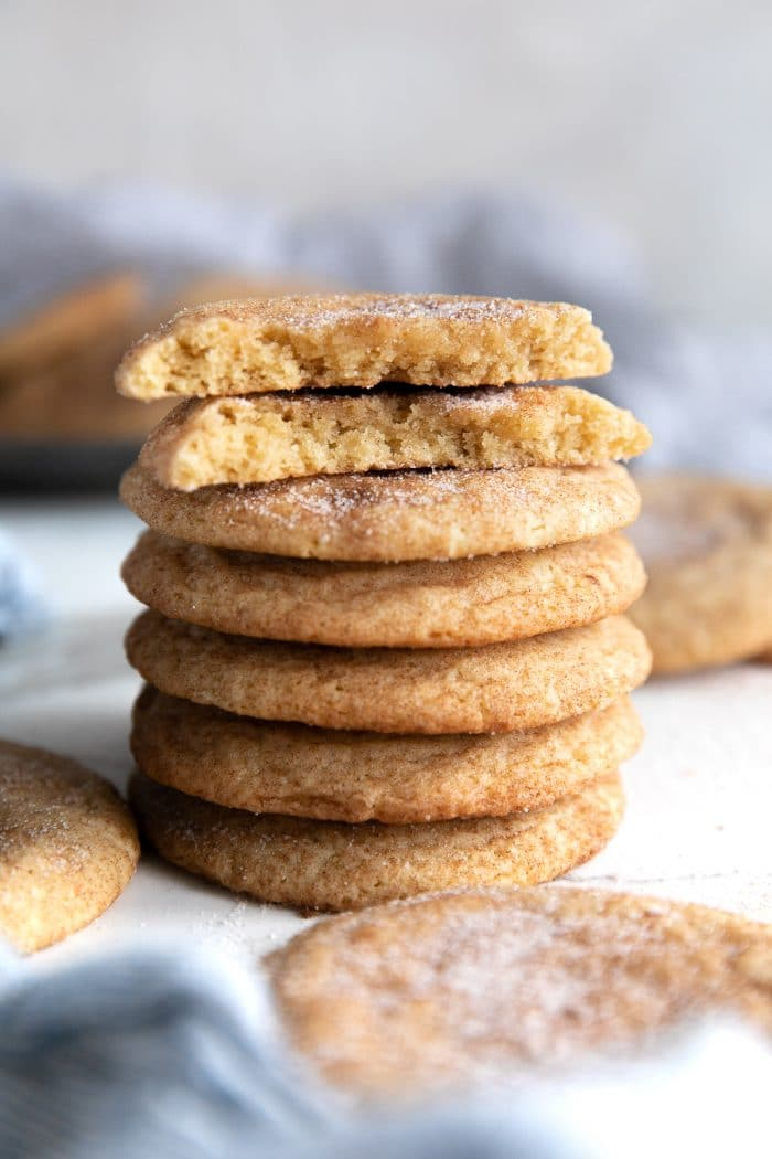 Stack of five snickerdoodle cookies topped with one snickerdoodle broken in half.