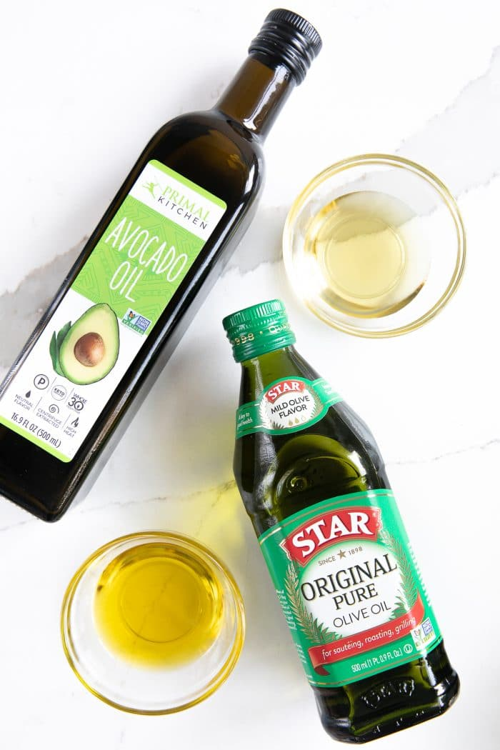 Bottle of avocado oil and olive oil with sample of each in small glass dishes