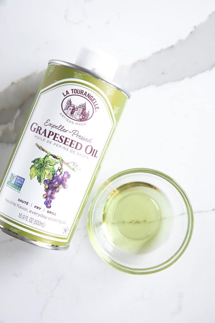 Bottle of grapeseed oil with a sample in a small glass bowl
