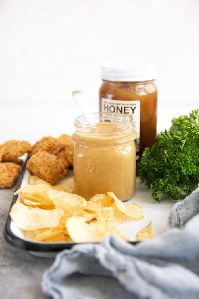 Honey mustard sauce on a white tray with potato chips, chicken nuggets, and a jar of honey in the background.