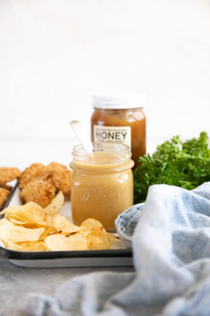 Easy honey mustard sauce in a small glass jar served with chips and chicken nuggets.