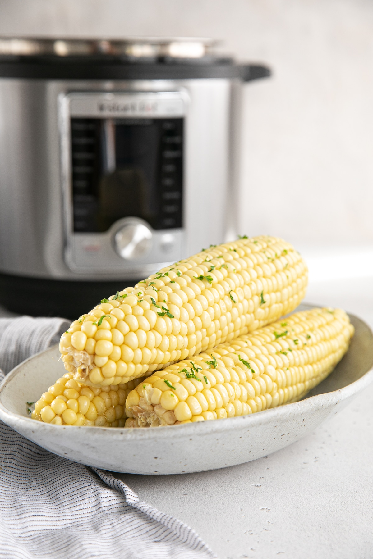 Three cooked and buttery ears of corn garnished with parsley.